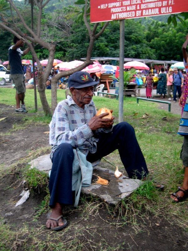 A MAN EATING A COCOANUT NEAR THE ENTRANCE TO THE MARKET