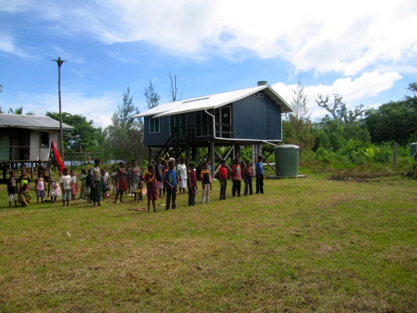 THE CHILDREN ARE ASSEMBLED IN FRONT OF THEIR SCHOOL WITH THEIR TEACHER TO PLEDGE ALLEGIANCE TO THE PNG FLAGPNG anthem and the PNG Pledge by the Watam school children