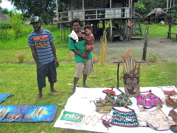 A COUPLE WITH THEIR BABY STANDING IN FRONT OF A TYPICAL HOUSE IN THE VILLAGE SELLING BAGS AND A MASKTO SELL TO THE VISITORS