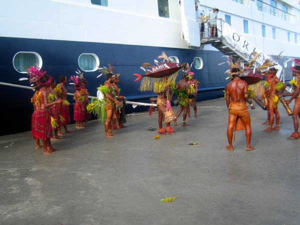 THE WOMEN WEAR COLORFUL GRASS SKIRTS AND THE HEAD DRESSES ARE MADE FROM THE CROWN PIGEON