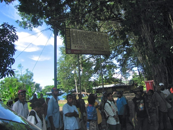 PEOPLE IN MADANG STANDING UNDER A SIGN OF TOWN REGULATIONS, NO GARBAGE THROWN IN THE STREET, NO SPITTING, AND GENERALLY KEEPING THE TOWN CLEAN