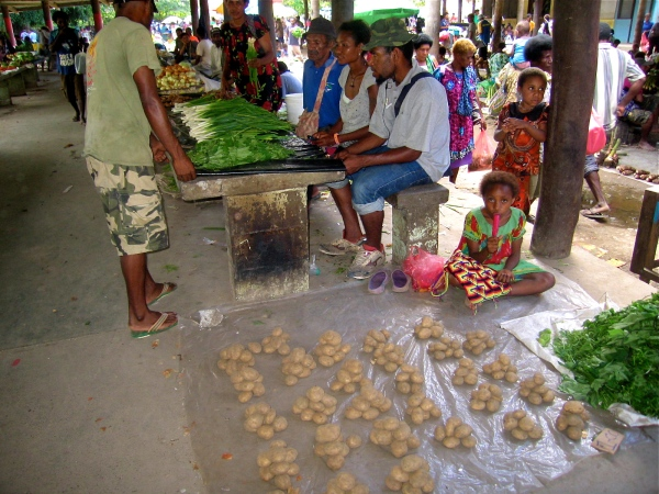 VENDORS AT THE MARKET WITH POTATOES AND OTHER VEGETABLES