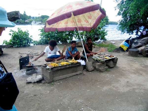 THESE WOMEN ARE SELLING FRIED FISH AND FRUIT