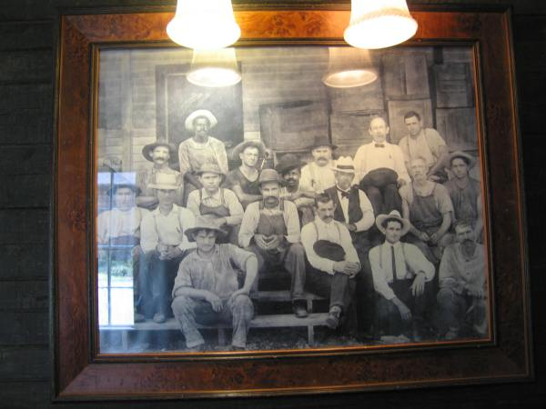 PHOTO OF JACK DANIELS (TOP LEFT) WITH HAT SURROUNDED BY HIS WORKERS