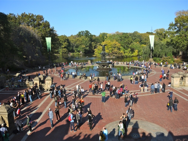 BETHESDA FOUNTAIN -  Bethesda Fountain is the central feature on the lower level of the terrace, constructed in 1859-64,which is enclosed within two elliptical balustrades. The pool is centered by a fountain sculpture designed by Emma Stebbins in 1868 and unveiled in 1873.Stebbins was the first woman to receive a public commission for a major work of art in New York. The bronze, eight-foot statue depicts a female winged angel touching down upon the top of the fountain, where water spouts and cascades into an upper basin and into the surrounding pool. It was the only statue in the park called for in the original design. Beneath her are four four-foot cherubs representing Temperance, Purity, Health, and Peace.Also called the Angel of the Waters, the statue refers to the Gospel of John, Chapter 5 where there is a description of an angel blessing the Pool of Bethesda, giving it healing powers. In Central Park the referent is the Croton Aqueduct opened in 1842, providing the city for the first time with a dependable supply of pure water: thus the angel carries a lily in one hand, representing purity, and with the other hand she blesses the water below. The base of the fountain was designed by the architect of all the original built features of Central Park, Calvert Vaux, with sculptural details, as usual, by Jacob Wrey Mould. In Calvert Vaux and Frederick Law Olmsted's 1858 Greensward Plan, the terrace at the end of the Mall overlooking the naturalistic landscape of the Lake was simply called The Water Terrace, but after the unveiling of the angel, its name was changed to Bethesda Terrace.