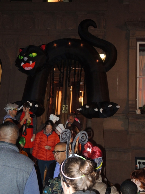 HALLLOWEEN REVELERS WITH BIG CAT DECORATION OVER THE ENTRANCE TO A BROWNSTONE WEST 69TH STREET