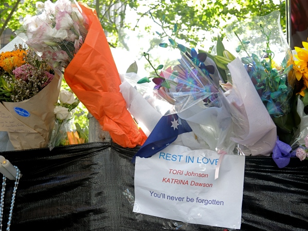 THE CAFE LINDT  IS HIDDEN BEHIND A WIRE FENCE WITH A BLACK MATERIAL AND  IS COVERED WITH BOUQUETS OF FLOWERS AND TRIBUTES