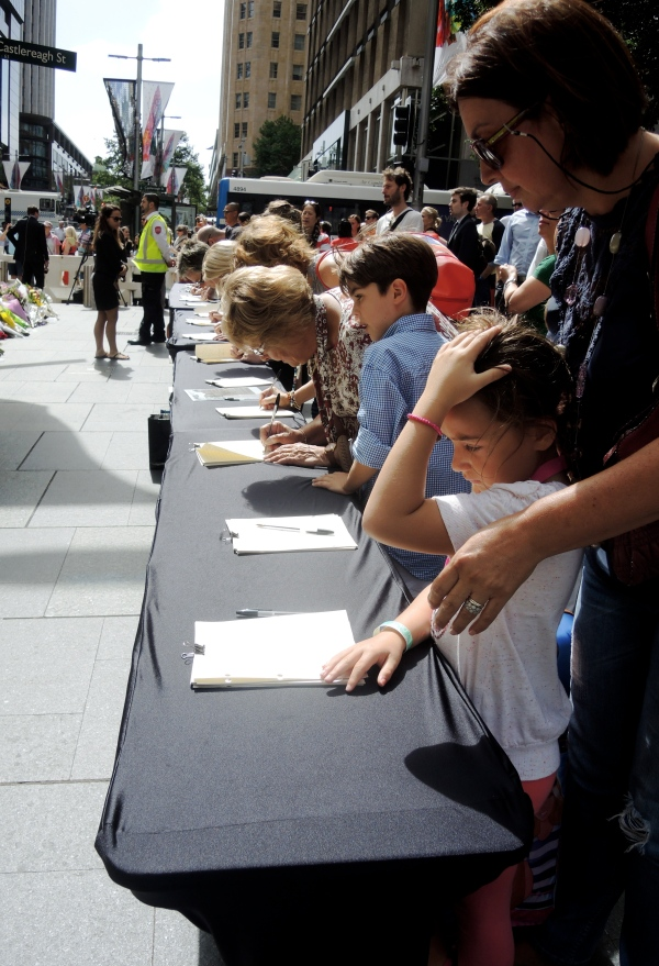 PEOPLE FILL OUT CONDOLENCE BOOKS