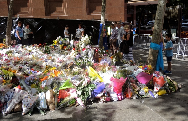 PEOPLE LOOK AT THE TRIBUTES AND FLOWERS