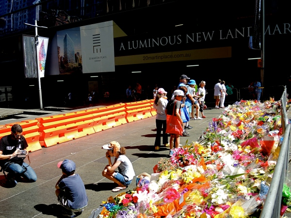 A FATHER AND HIS TWO CHILDREN PAUSE BESIDE THE BOUQUETS  AND OTHERS LOOK AT THE NOTES  THAT PEOPLE HAVE LEFT