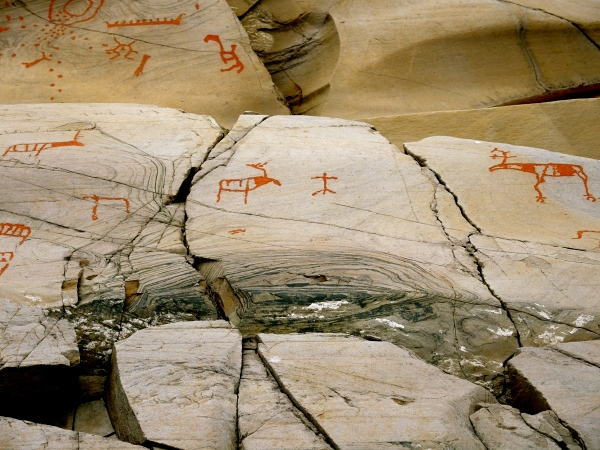 ALTA MUSEUM ROCK CARVING - REINDEER N THE FOREGROUND AND ON TOP MEN IN A FISHING BOAT AND A HUNTER WITH A CLUB